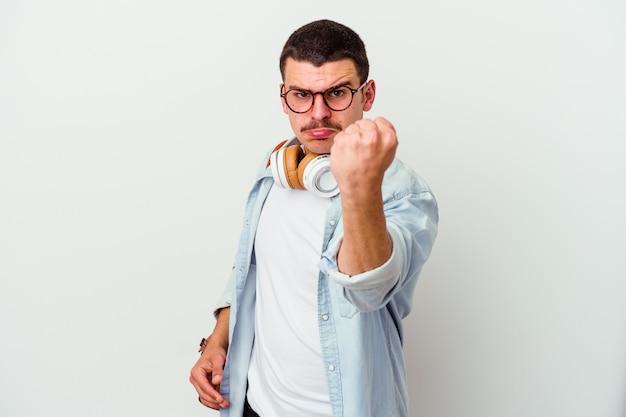 正面に拳、攻撃的な表情を示す白い壁に分離された音楽を聴いている若い学生男性