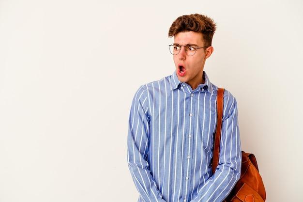 Молодой студент человек на белом шокирован из-за чего-то, что она видела.