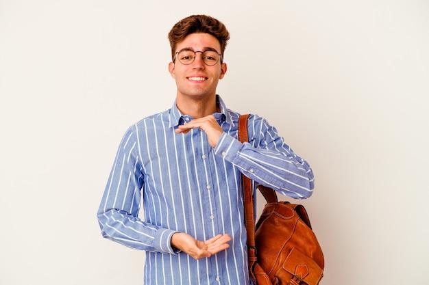 Молодой студент человек на белом, что-то держит обеими руками, презентация продукта.