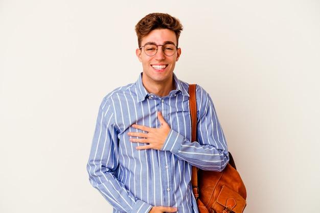 Молодой студент человек на белом счастливо смеется и весело держит руки на животе.