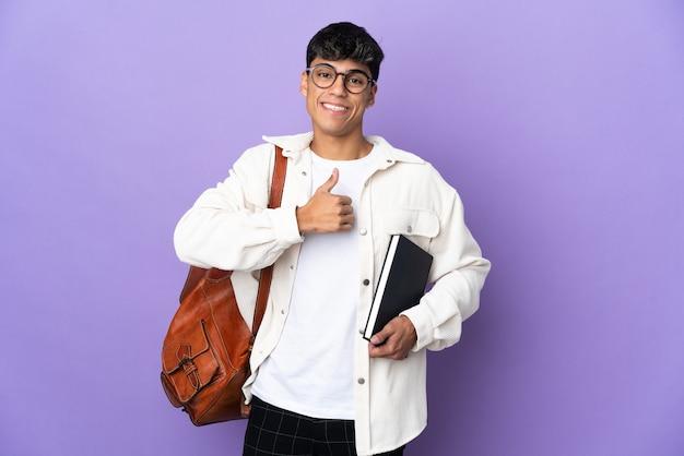 親指を立てるジェスチャーを与える孤立した紫色の壁の上の若い学生男