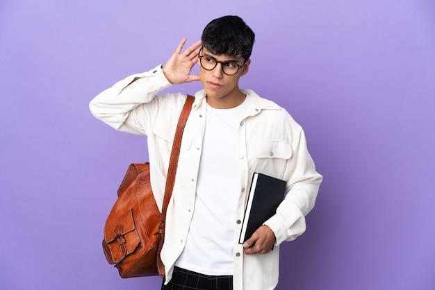 귀에 손을 넣어 뭔가를 듣고 고립 된 보라색 벽 위에 젊은 학생 남자