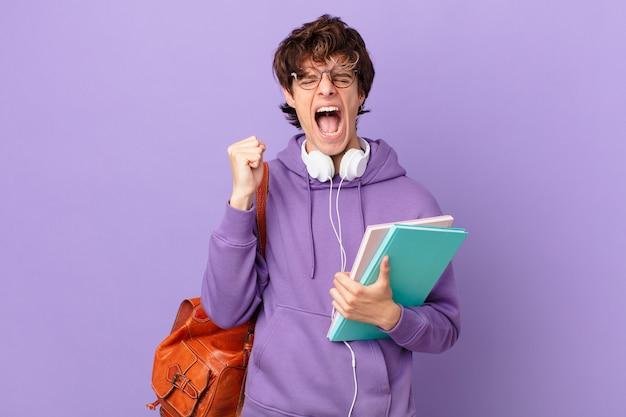 Молодой студент человек агрессивно кричит с сердитым выражением лица