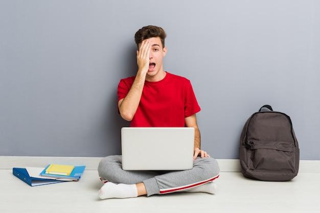 Молодой студент человек сидит на полу своего дома, держа ноутбук