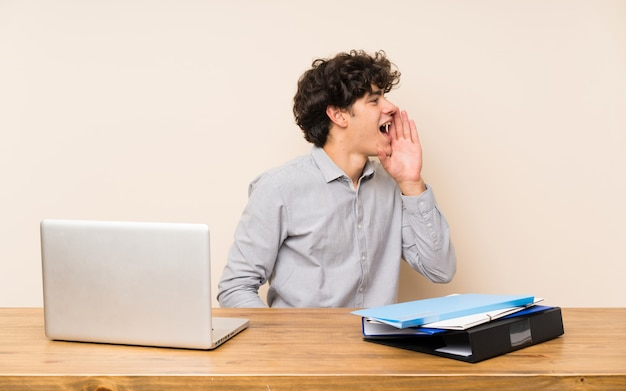 Young student man with a laptop shouting with mouth wide open to the lateral