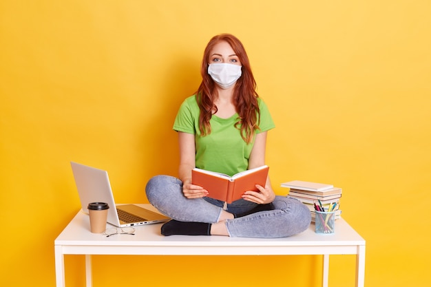Young student in medical mask studying at home while quarantine, bored of distance learning, sitting with crossed legs on white table with book in hands.