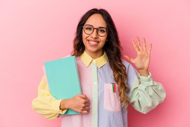 指で 5 番を示す陽気な笑みを浮かべてピンクの背景に分離された若い学生メキシコ人女性。
