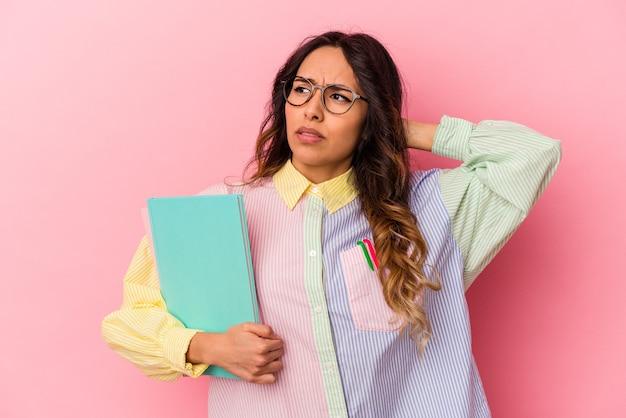 젊은 학생 멕시코 여자 머리 뒤로 만지고 생각 하 고 선택 분홍색 배경에 고립.