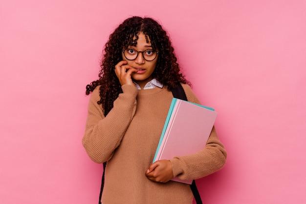 Молодой студент смешанной расы женщина, изолированные на розовом фоне, кусая ногти, нервная и очень тревожная.