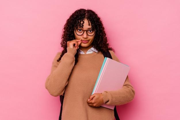 비밀을 유지하는 입술에 손가락으로 분홍색 배경에 고립 된 젊은 학생 혼혈 여자.