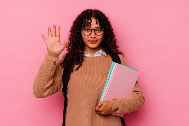 ピンクの笑顔で陽気な若い学生の混血の女性は、指で5番を示しています。