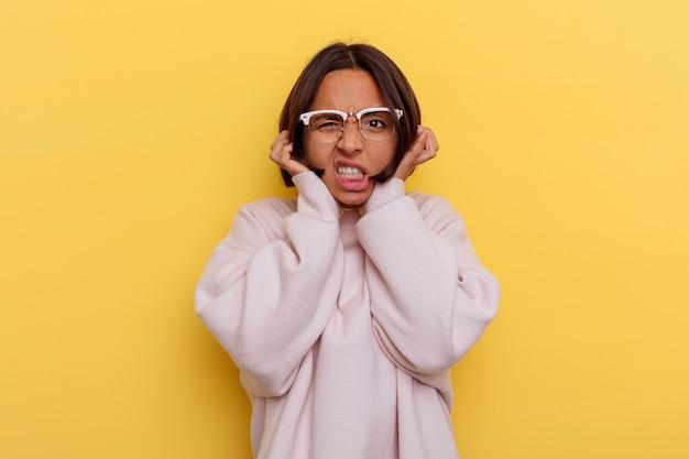 若い学生の混血の女性は、手で耳を覆う黄色の背景に分離されました。