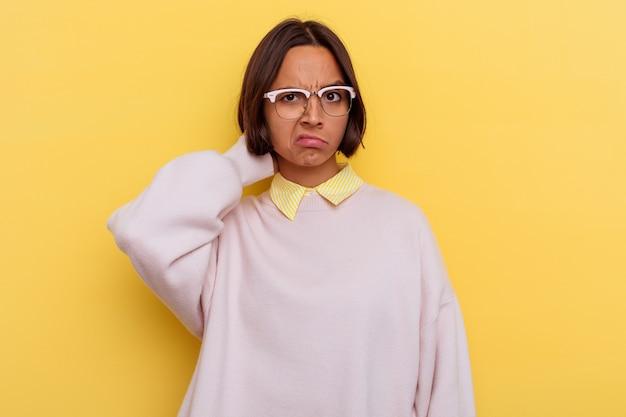 Молодая женщина смешанной расы студента изолированная на желтом фоне касаясь затылка, думая и делая выбор.