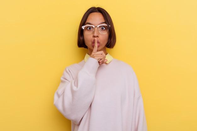 비밀을 유지하거나 침묵을 요구하는 노란색 벽에 고립 된 젊은 학생 혼혈 여자.