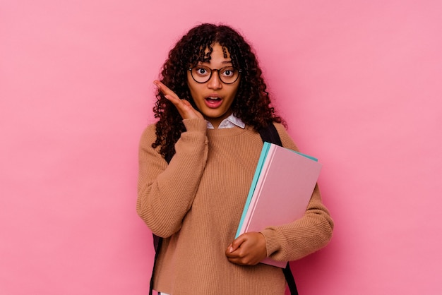 Young student mixed race woman isolated on pink wall surprised and shocked.