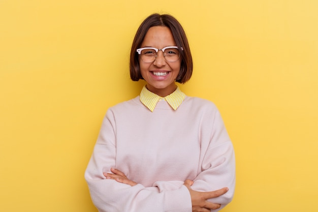 Young student mixed race woman isolated on yellow wall laughing and having fun.