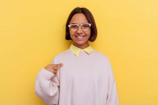 Young student mixed race woman isolated on yellow wall person pointing by hand to a shirt copy space, proud and confident