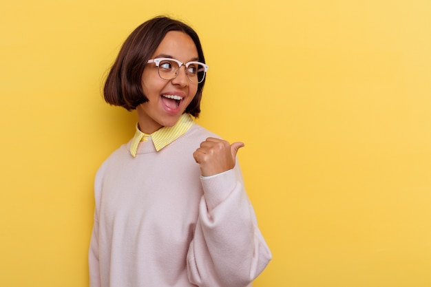 Young student mixed race woman isolated on yellow wall points with thumb finger away, laughing and carefree.