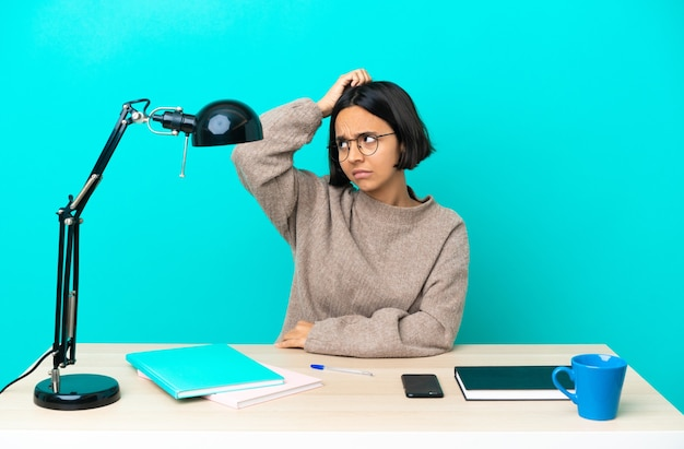 頭を掻きながら疑問を持ってテーブルを勉強する若い学生混血女性
