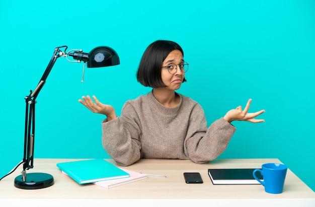 疑問を持ってテーブルを勉強する若い学生混血女性