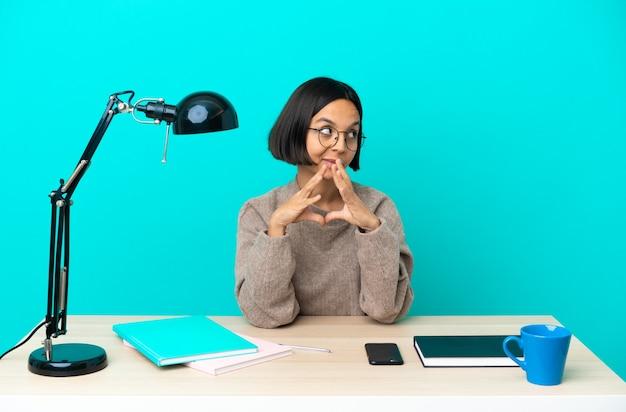 何かを企んでいるテーブルで勉強する若い学生混血女性