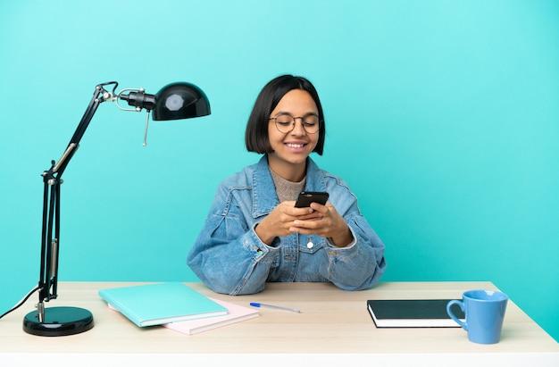 Молодая студентка смешанной расы изучает стол, отправляя сообщение с мобильного телефона