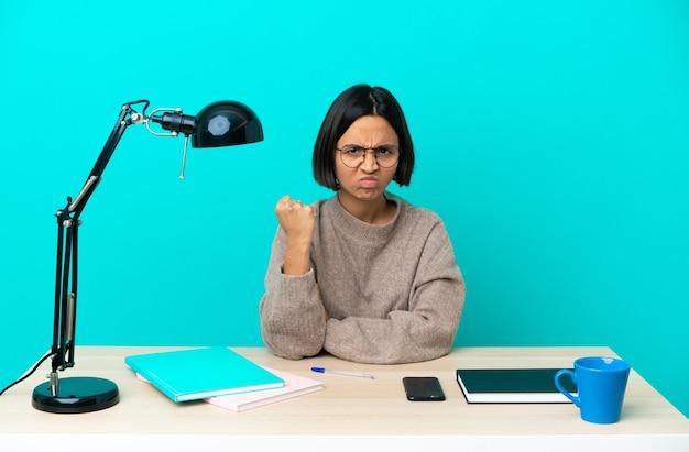 Молодой студент смешанной расы женщина изучает стол с несчастным выражением лица