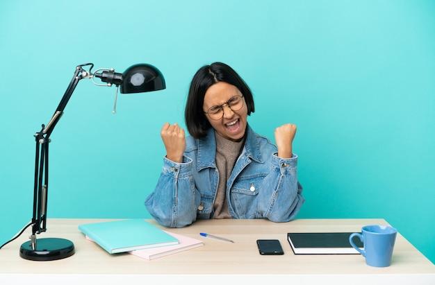 Молодой студент смешанной расы женщина учится на столе празднует победу