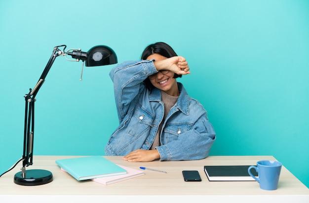 손으로 눈을 덮고 테이블에서 공부하는 젊은 학생 혼혈 여자