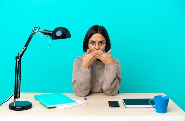 Молодой студент смешанной расы женщина учится на столе, закрывая рот руками