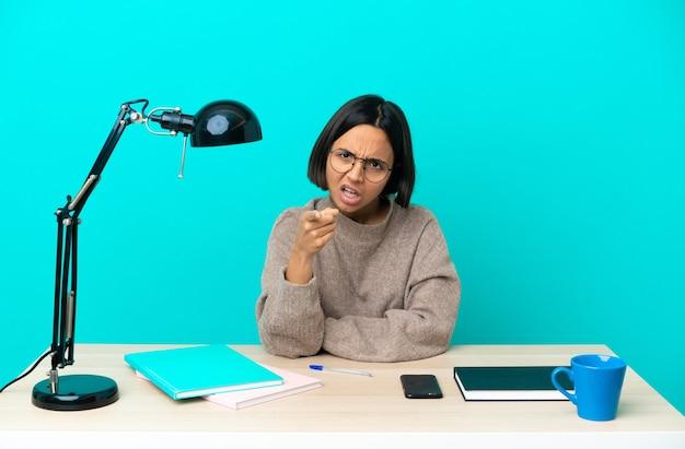 Молодой студент смешанной расы женщина учится на столе разочарована и указывая вперед