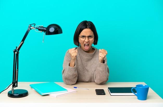 Молодая студентка смешанной расы учится на столе, разочарованная плохой ситуацией