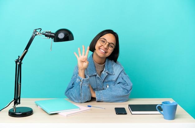 Молодой студент смешанной расы женщина учится на столе счастлива и считает четыре пальцами