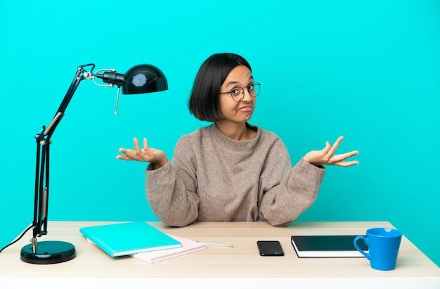 Молодой студент смешанной расы женщина учится на столе счастливым и улыбается