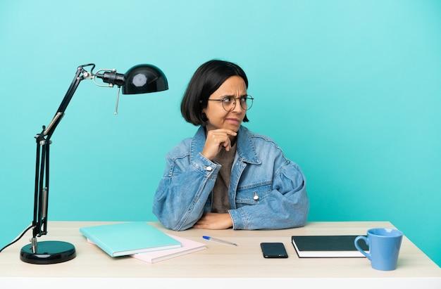 Молодой студент смешанной расы женщина учится на столе, сомневаясь и думая