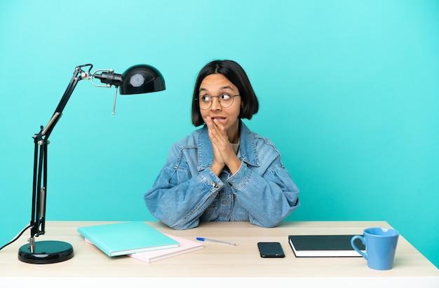 Молодой студент смешанной расы женщина учится на столе, сомневаясь, глядя вверх