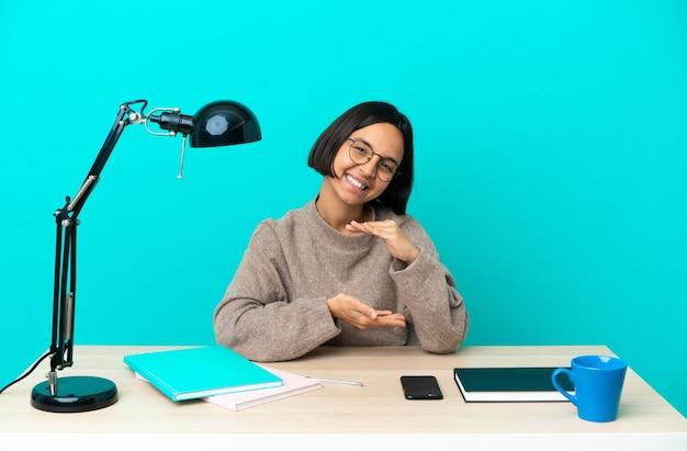 Молодая студентка смешанной расы учится на столе, держа на ладони воображаемое пространство, чтобы вставить объявление
