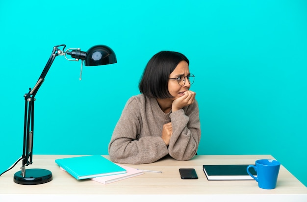 Молодой студент смешанной расы женщина учится на столе немного нервничает