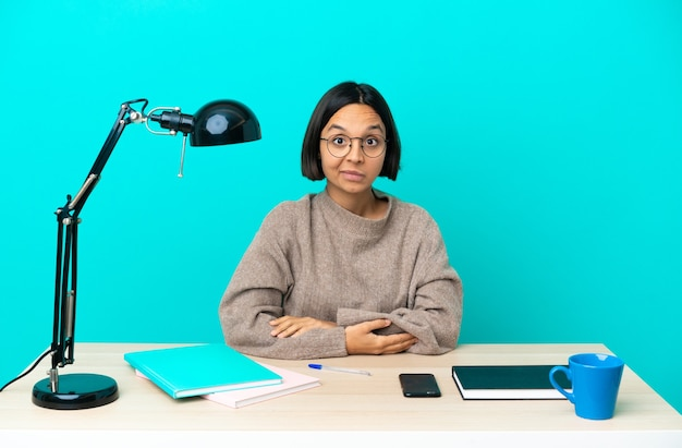 Молодой студент смешанной расы женщина учится на столе смеется