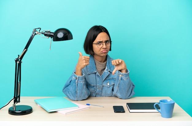 Молодой студент смешанной расы женщина учится на столе, делая хороший плохой знак. не определился, да или нет