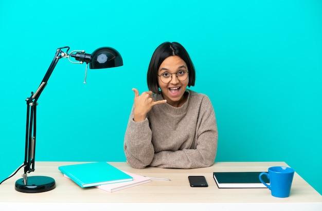 Молодой студент смешанной расы женщина учится на столе, делая телефонный жест. перезвони мне знак