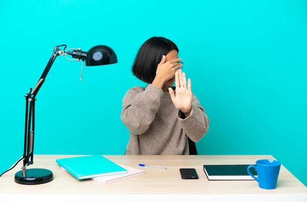 Молодой студент смешанной расы женщина учится на столе, делая жест остановки и закрывая лицо