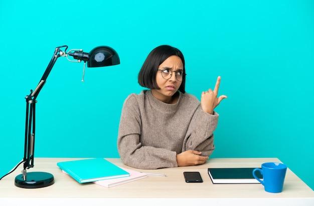 Молодой студент смешанной расы женщина учится на столе, делая жест безумия, положив палец на голову