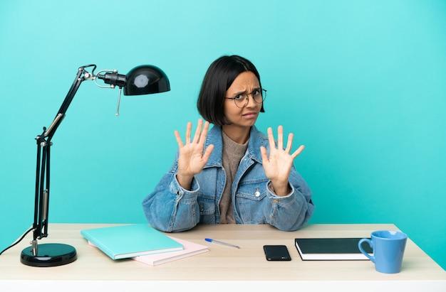 Молодой студент смешанной расы женщина учится на столе нервно протягивает руки вперед