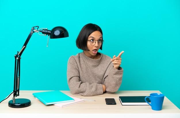Молодой студент смешанной расы женщина учится на столе, указывая в сторону