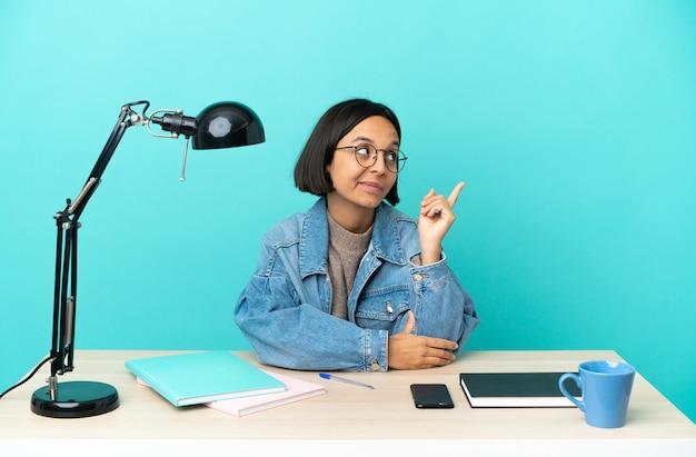 Молодой студент смешанной расы женщина учится на столе, указывая на отличную идею