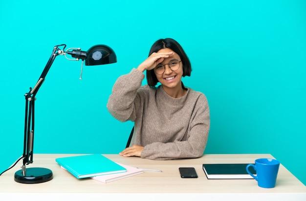 Молодой студент смешанной расы женщина учится на столе, салютуя рукой с счастливым выражением лица