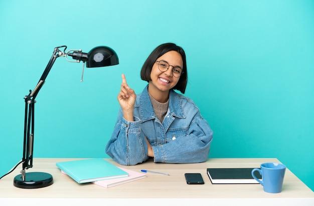 最高の兆候を示して指を持ち上げてテーブルで勉強している若い学生混血の女性