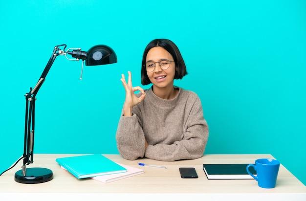 Молодой студент смешанной расы женщина учится на столе, показывая знак ок с пальцами