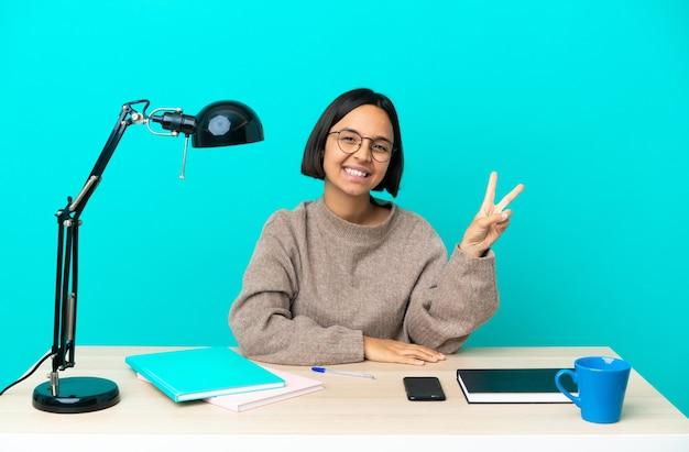 Молодой студент смешанной расы женщина учится на столе улыбается и показывает знак победы